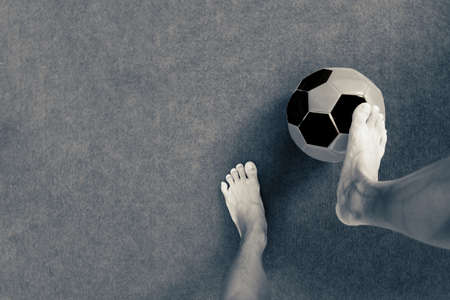 The foot of the footballer is stepping on the football. Фото со стока