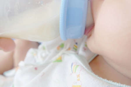 close up of The baby is eating milk from the bottle with happily.