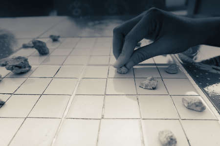 Hand of Asian woman picked the stones to play checkers.