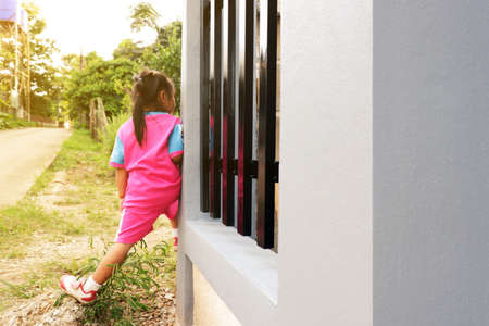 The girl is playing hidden behind the fence. Standard-Bild