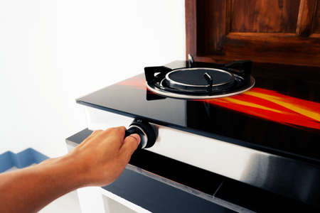 Use the hand to twist the switch of the gas stove.