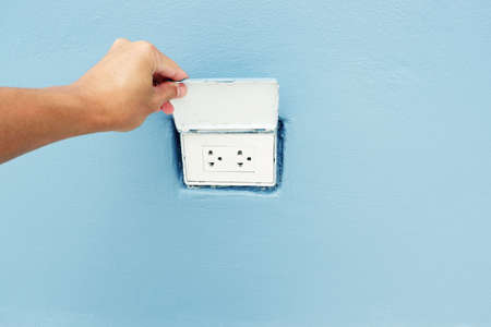 hand is open lid of Electrical outlet boxes with Installed in the wall Stock Photo