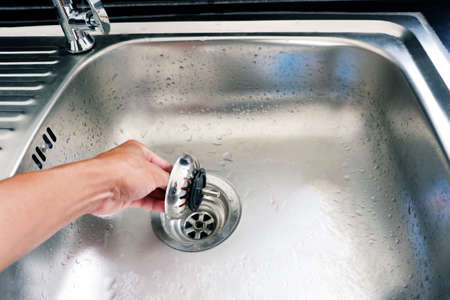 hand is catch and pull lid of drain hole of the sink
