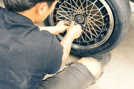 The mechanics are tightening the wheel nuts to change the wheels. Stok Fotoğraf