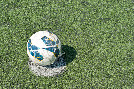 the old football at penalty mark on artificial grass photo