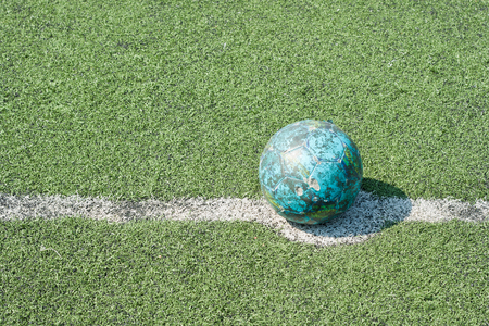the old football at kickoff mark on artificial grass photo