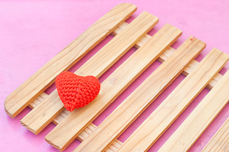 red heart put on wood panel on the pink table