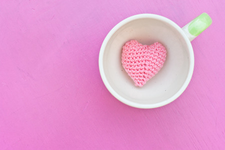Pink heart in the coffee cup on pink table photo