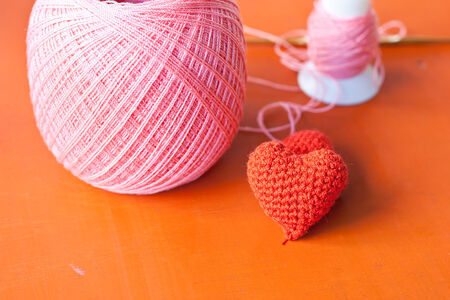 the heart knit with red yarn on orange table  Stockfoto