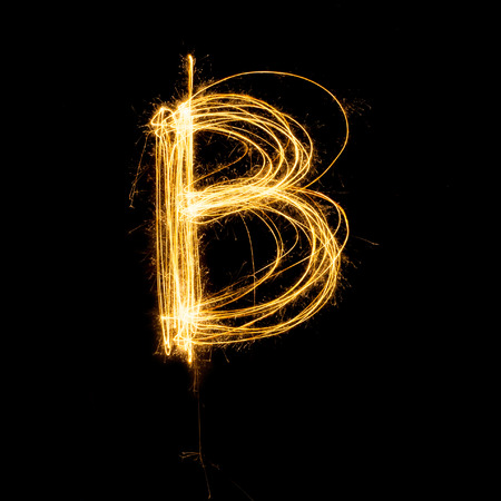Sparkler firework light alphabet B with uppercase isolated on black background. Stock Photo