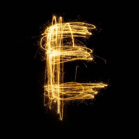 Sparkler firework light alphabet E with uppercase isolated on black background. Stock Photo