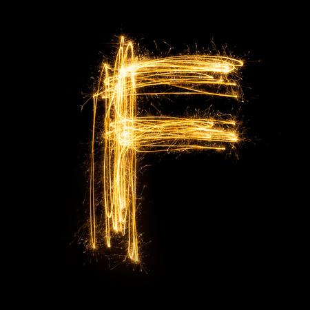 Sparkler vuurwerk licht alfabet F met hoofdletters geïsoleerd op een zwarte achtergrond.