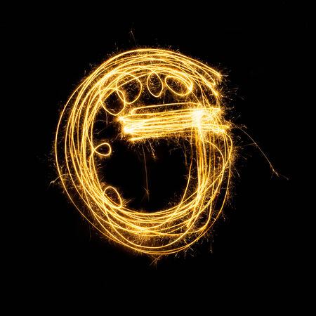g: Sparkler firework light alphabet G with uppercase isolated on black background.