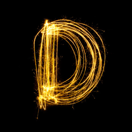 d: Sparkler firework light alphabet D with uppercase isolated on black background. Stock Photo
