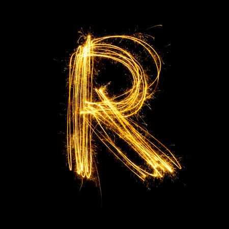 Sparkler firework light alphabet R with uppercase isolated on black background. Standard-Bild