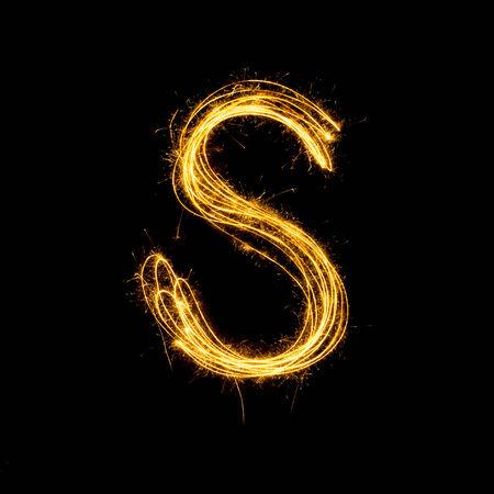 Sparkler vuurwerk lichte alfabet S met hoofdletters geïsoleerd op een zwarte achtergrond. Stockfoto