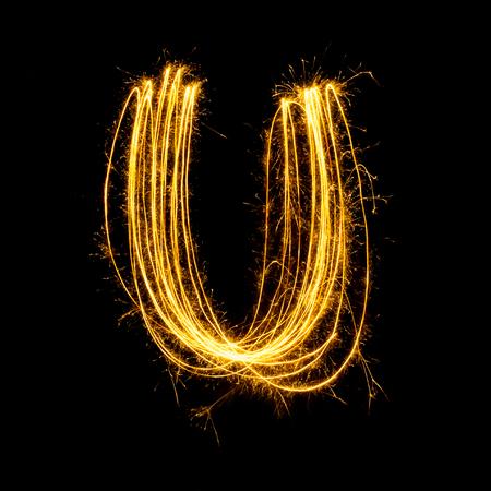 Sparkler firework light alphabet U with uppercase isolated on black background.