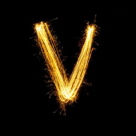 Sparkler firework light alphabet V with uppercase isolated on black background.