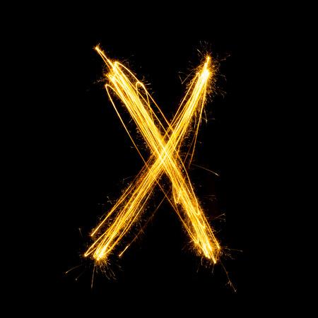 Sparkler firework light alphabet X with uppercase isolated on black background. Standard-Bild