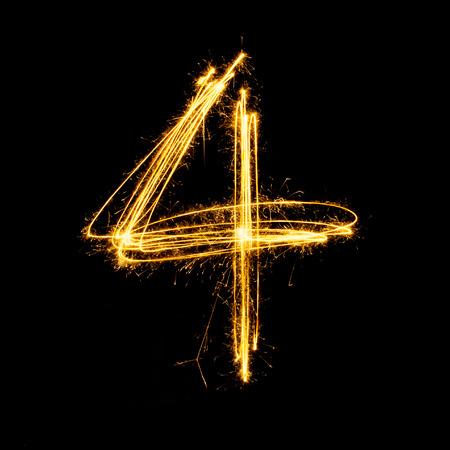 Sparkler firework light alphabet number 4 isolated on black background. Standard-Bild