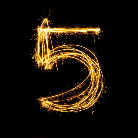 and  celebrate: Sparkler firework light alphabet number 5 isolated on black background.