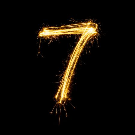 Sparkler vuurwerk licht alfabet nummer 7 geïsoleerd op een zwarte achtergrond.