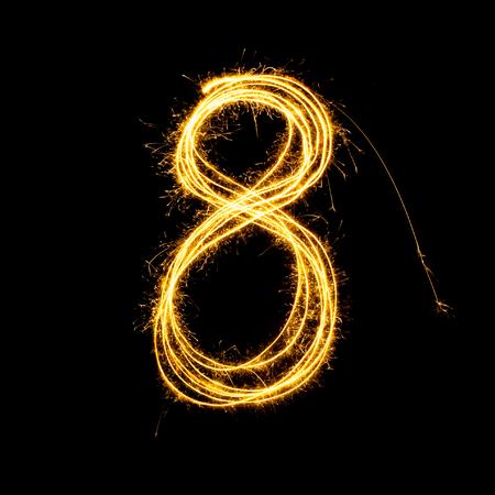 Sparkler vuurwerk licht alfabet nummer 8 geïsoleerd op een zwarte achtergrond. Stockfoto