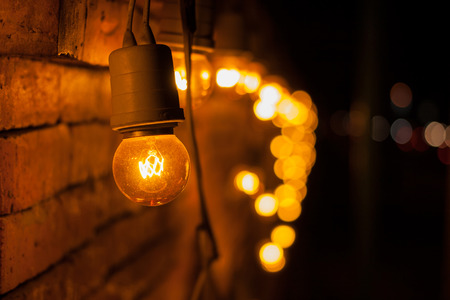 tungsten: Closeup of tungsten lamp decorated on brick wall with bokeh light background..