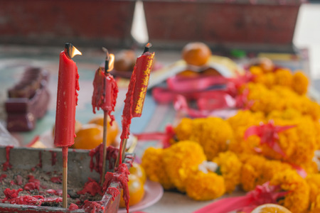 taper: Burning red candle in pot at chinese shrine for making merit in chinese new year festival.