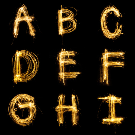 Collection of sparkler firework light alphabet isolated on black background.