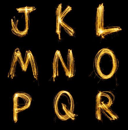 Collection of sparkler firework light alphabet isolated on black background.
