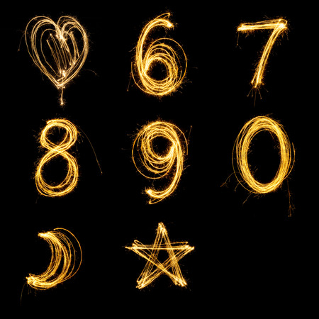 Collection of sparkler firework light alphabet number and sign isolated on black background.