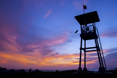 A lifeguard tower silhouette against a sunset sky.  Stock Photo