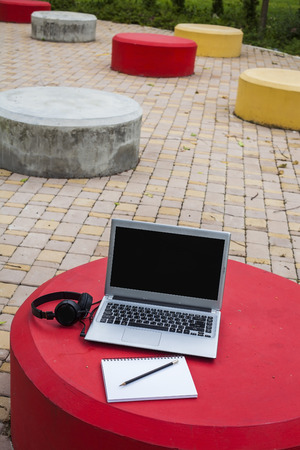 Laptop on the red cement table in the park