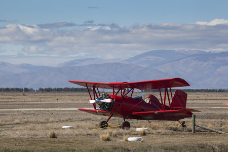 Red classic plane on a gold grass field Stock Photo