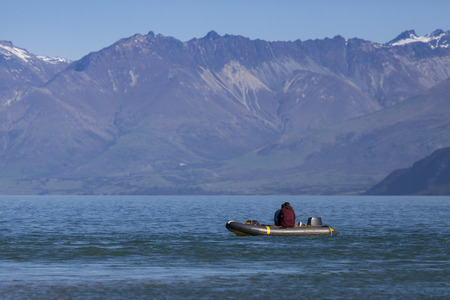 Two fishing man on the boat at beautiful lake and mountain background