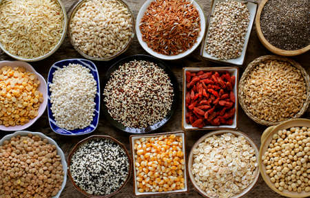 Variety kinds of dry organic white and brown cereal and grain seed on grunge background