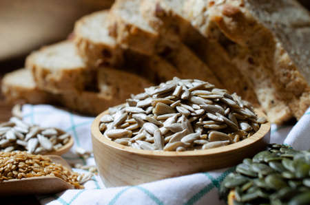 Closed up organic sunflower seeds in wooden bowl over blur whole wheat bread, golden flax and pumpkin seed on white table cloth in dark brown tone Stock Photo