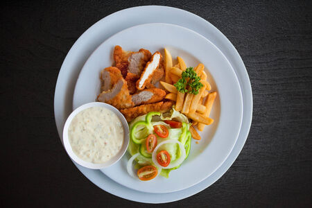 Plated lunch of chicken strips, french fries with ketchup and dipping sauce. photo