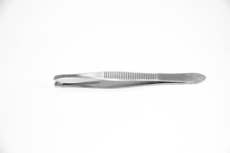 Little metal hair tweezers isolated over white background. photo