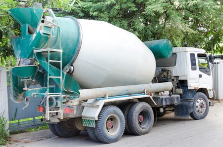 concrete mixer truck: Concrete mixer truck with green cab over trees.