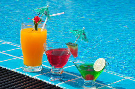 infinity pool: Orange juice and Cocktails near the swimming pool . Stock Photo