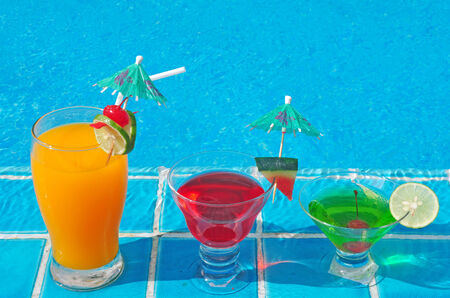 Orange juice and Cocktails near the swimming pool . photo