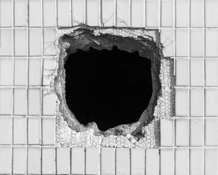 Hole on the old white wall. Picture can be used as a background