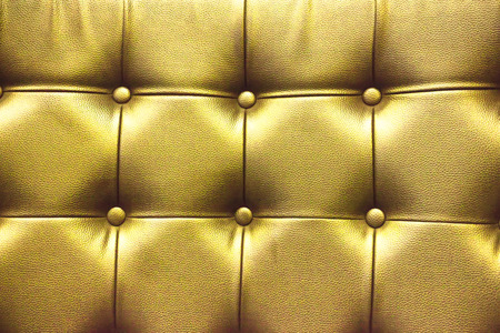 Closeup texture of vintage gold leather sofa for background.