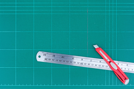 A ruler and cutter on green cutting mat isolate for text