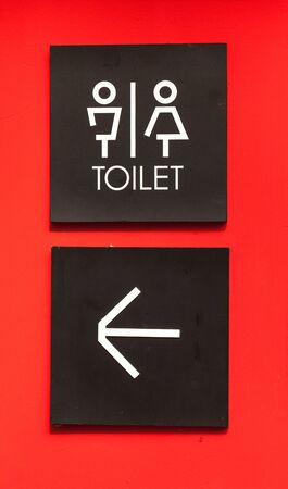 loo: Unisex restroom or toilet and arrow sign on red wall style boutique .