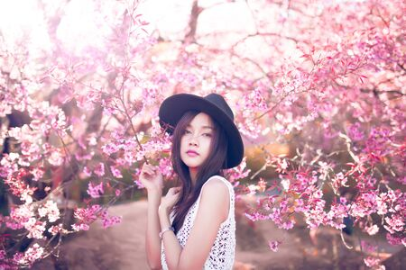 Beautiful asian women with sakura flower in thailand.