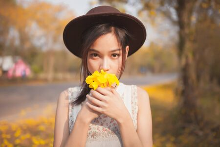 asian natural: Asian pretty girl surrounded by the yellow flowers in summer . Stock Photo