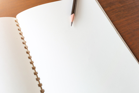 Blank note book with pencil on wooden table background concept and Idea for write your text here.
